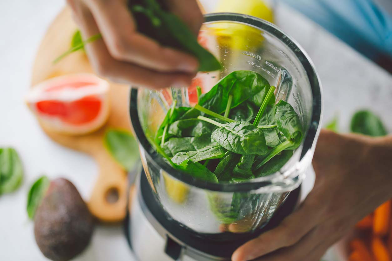 hand putting spinach in personal blender