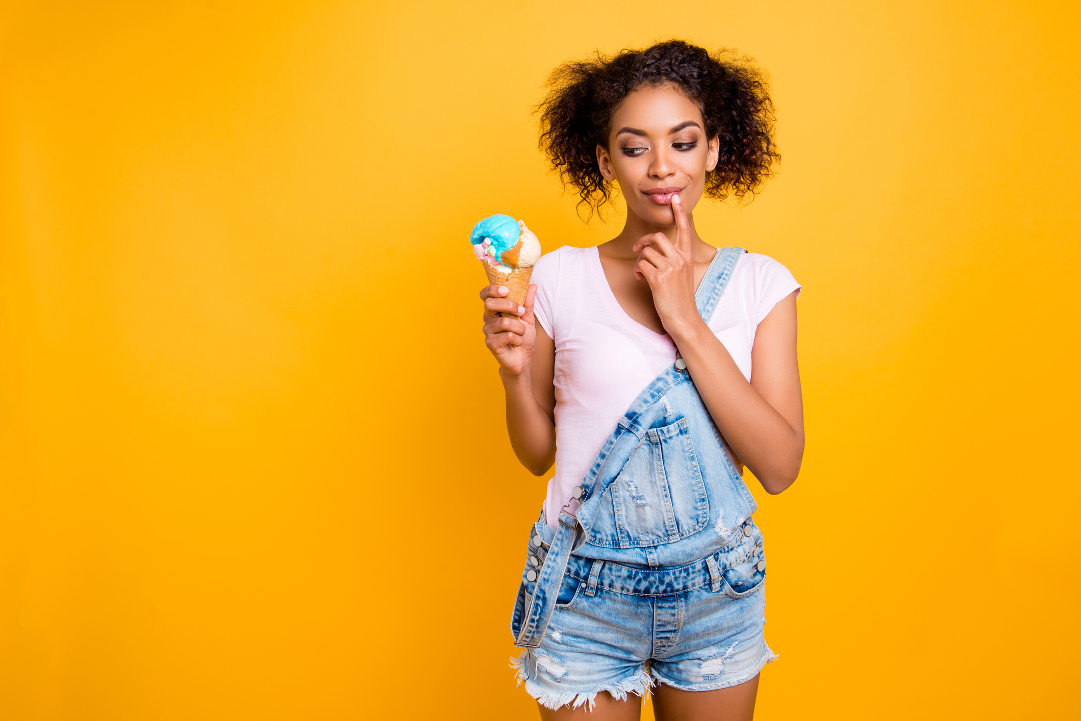 A young woman holds an ice cream cone on a yellow background