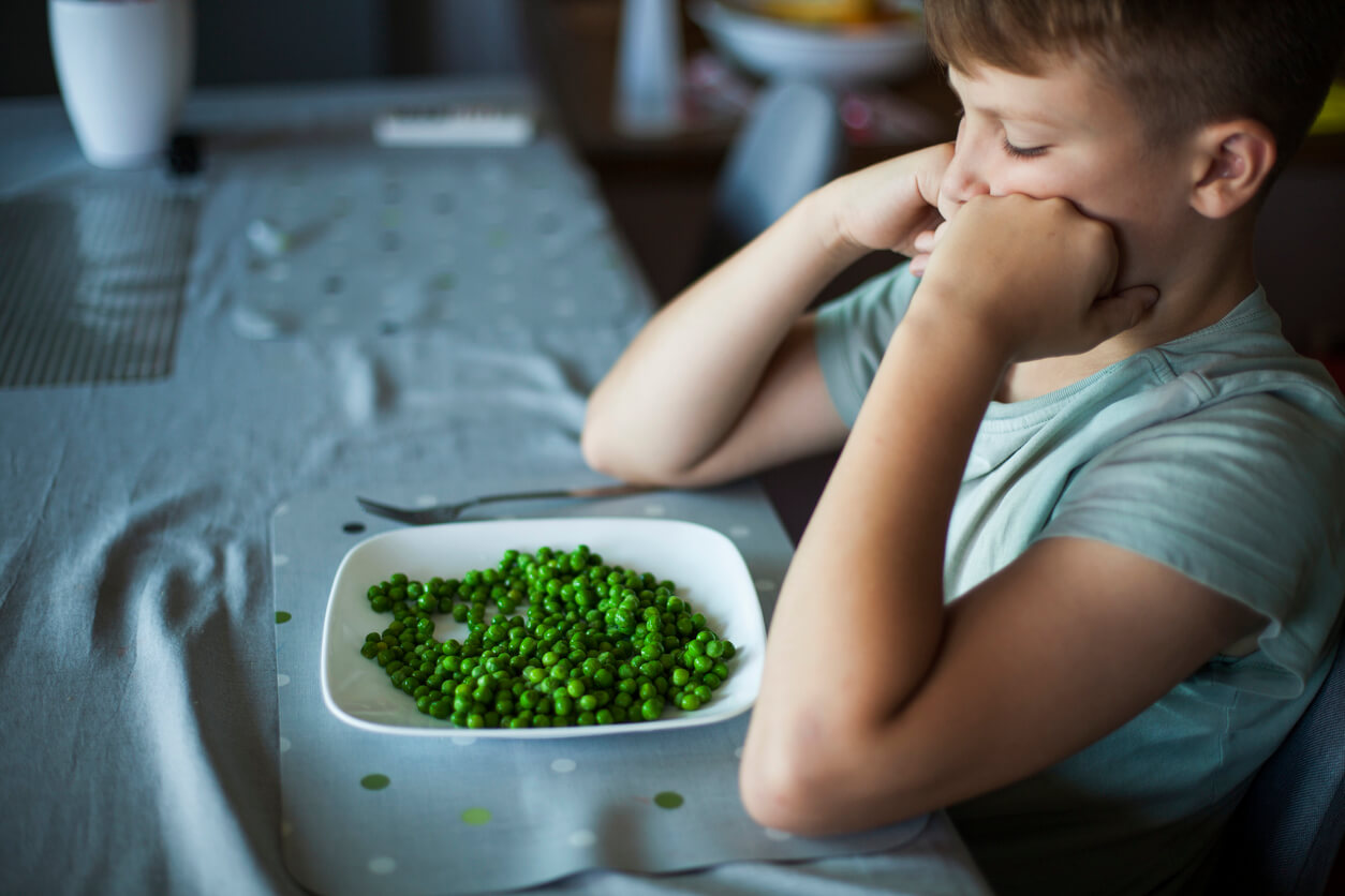 boy sitting in front of a plate of green peas