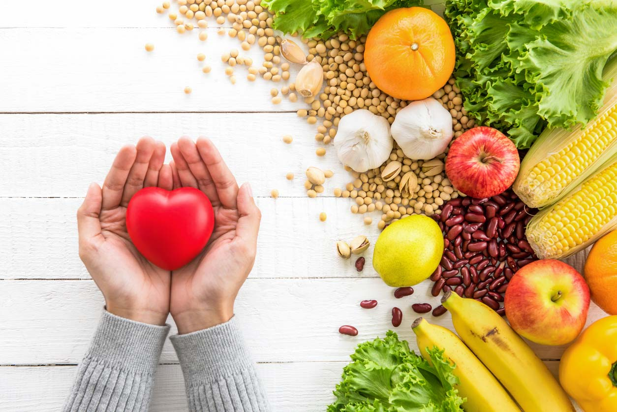 hands holding heart next to healthy foods on table