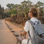 Young woman on bicycle in ancient temple complex in Cambodia