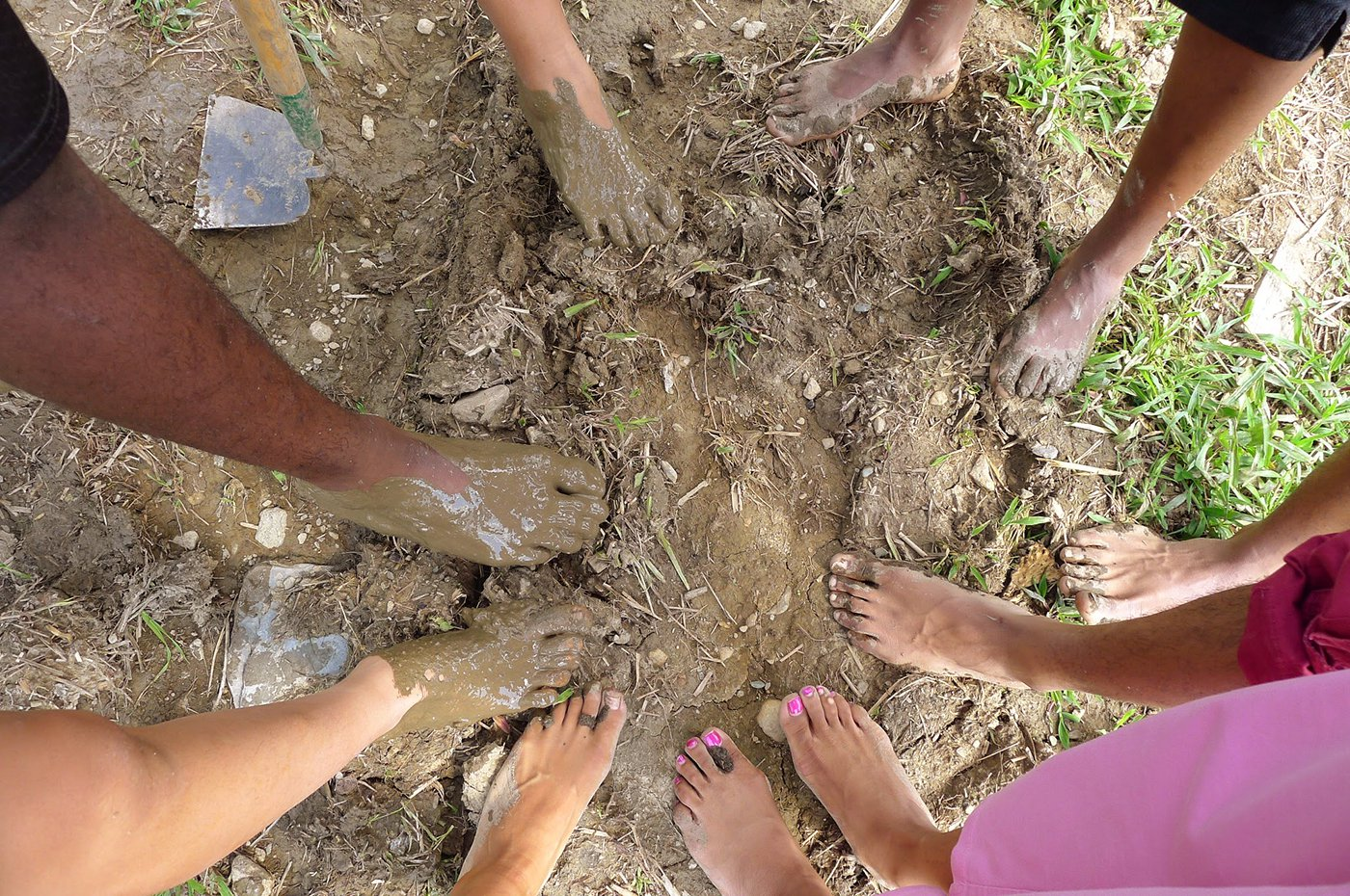 Teen participants take their shoes off to experience the mud on their feet.