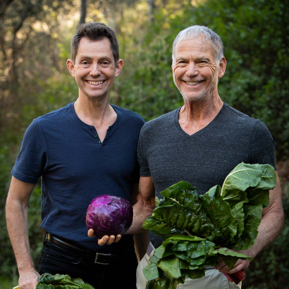 John and Ocean Robbins holding veggies